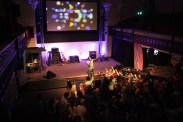 A photo of Guvna B, on stage mid-performance. Take from the balcony, high up.