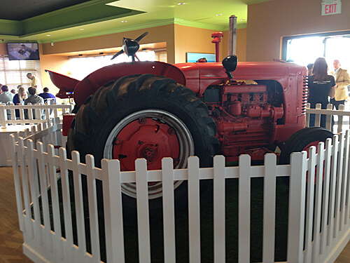Big red tractor and white picket fences inside Plow & Harvest.
