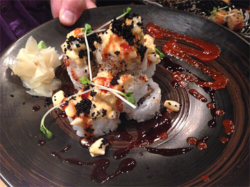 Volcano rolls - hot spicy chopped scallops, squid and tobiko sauce over an avocado and eel roll - $16.95