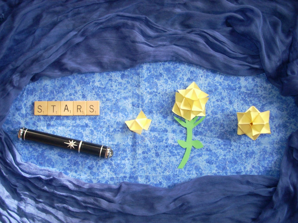 "Photo of Scrabble tiles spelling, ""Stars"", a tiny telescope and an origami fortune teller, flower and star"