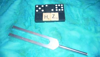 Image shows a tuning fork with dominoes showing the numbers 5,2, & 8. Two scrabble tiles show HZ for hertz