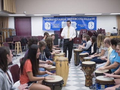 Dr. Kevin Shorner-Johnson walks through an aisle of tall drums with college age drummers.