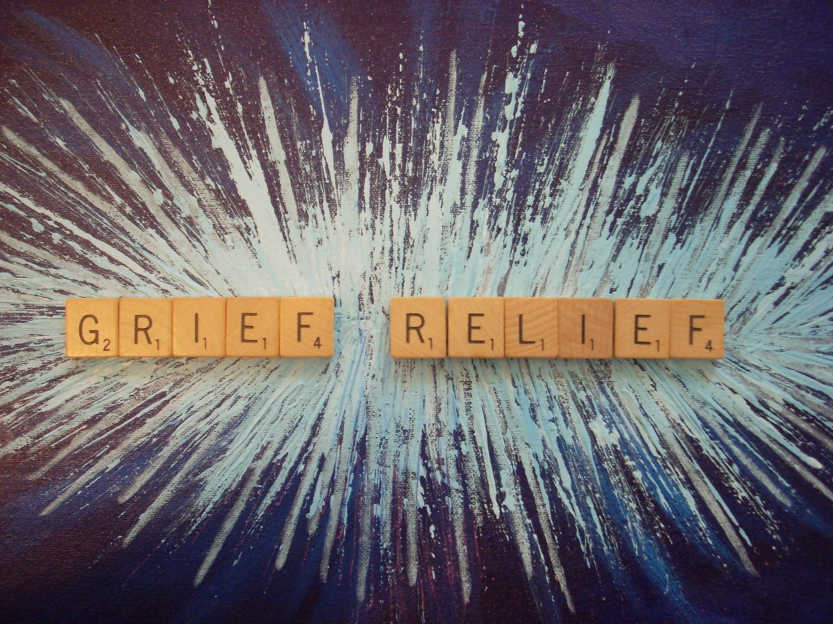 """Scrabble tiles spelling """"Grief Relief"""" laying on a painted blue surface indicative of bright light"""