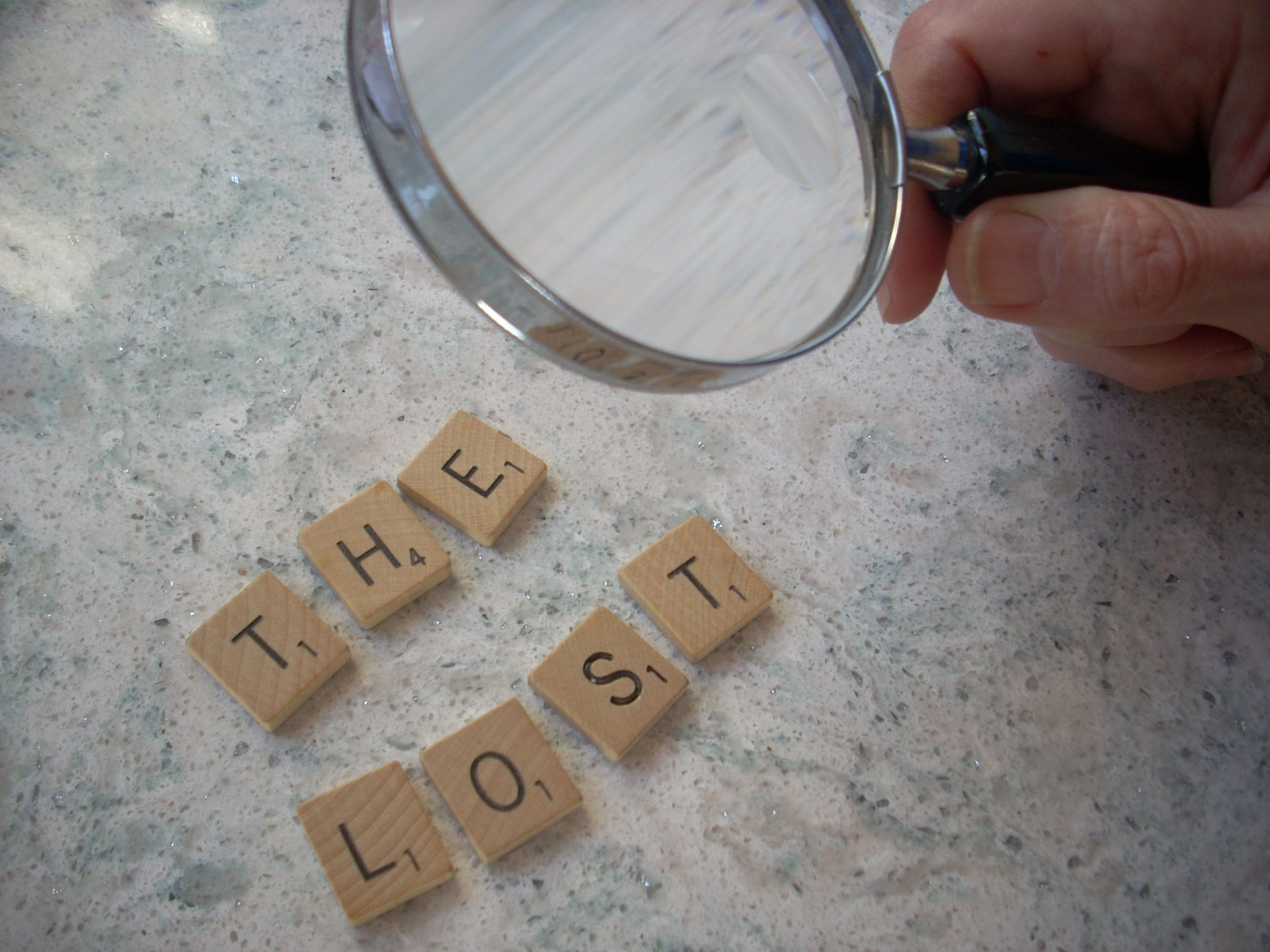"hand holding a magnifying glass focusing on Scrabble tiles spelling ""The Lost"""