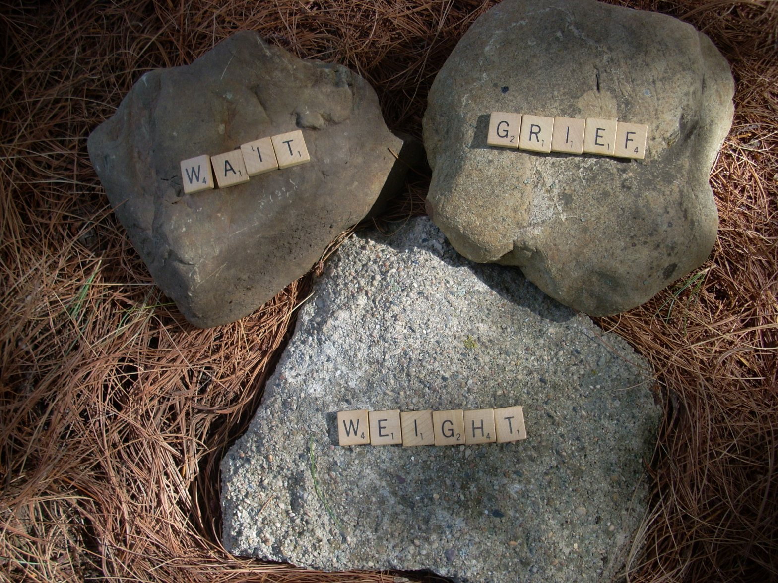photo of three large rocks with each one displaying one word of the three word title: Wait Grief Weight