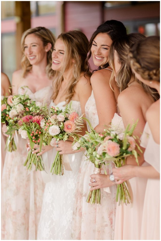 Beautiful bridesmaids wearing blush dresses on the patio of the Barn at Gibbet Hill.  Photos by Linda Barry Photography, a Boston based wedding photographer.