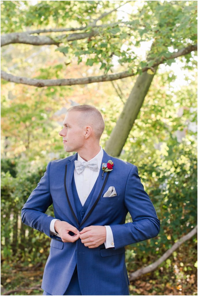 Groom buttoning his jacket at his fall wedding at the Dan'l webster inn.