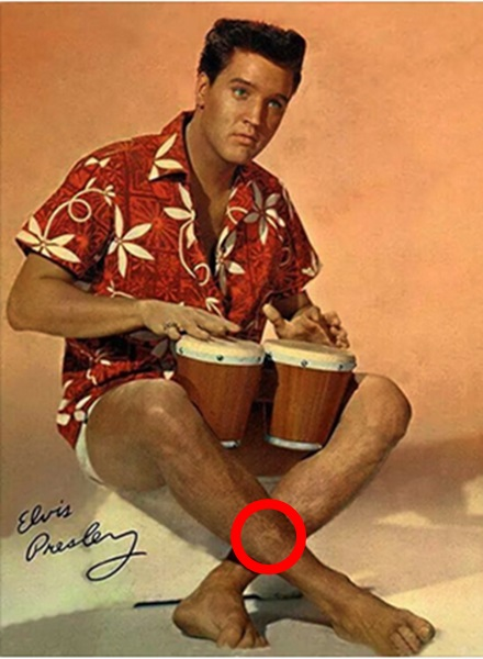 Movie still with makeup on Elvis' leg to cover scar circle in red