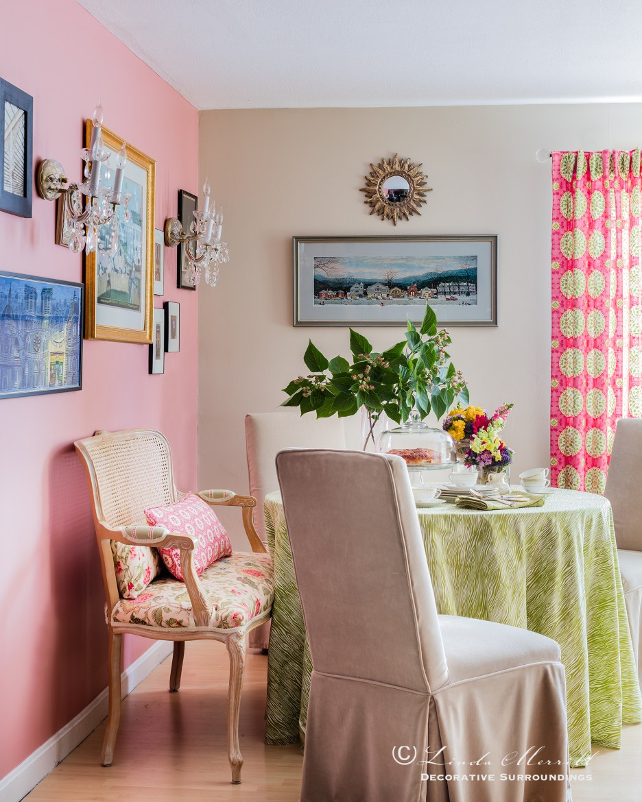 A dining space with green tablecloth, slipcovered chairs, pink and beige walls and pink drapery.