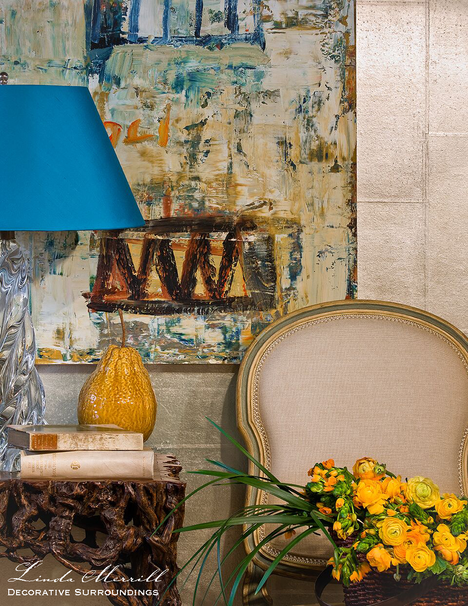 A modern vignette with modern art, blue lamp shade, faux bois side table, yellow flowers and French side chair