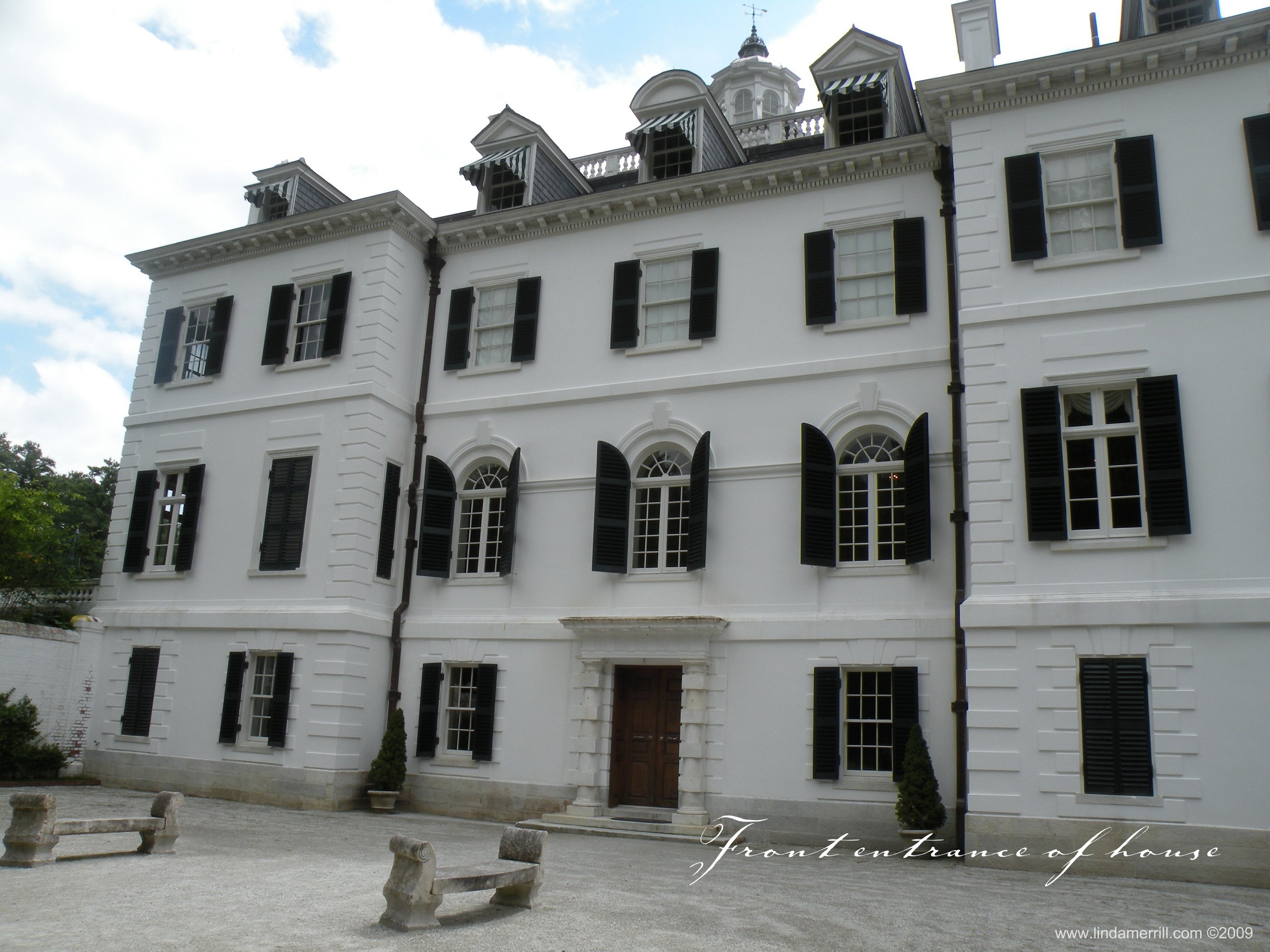 The exterior of The Mount from the forecourt. A white house with black shutters.