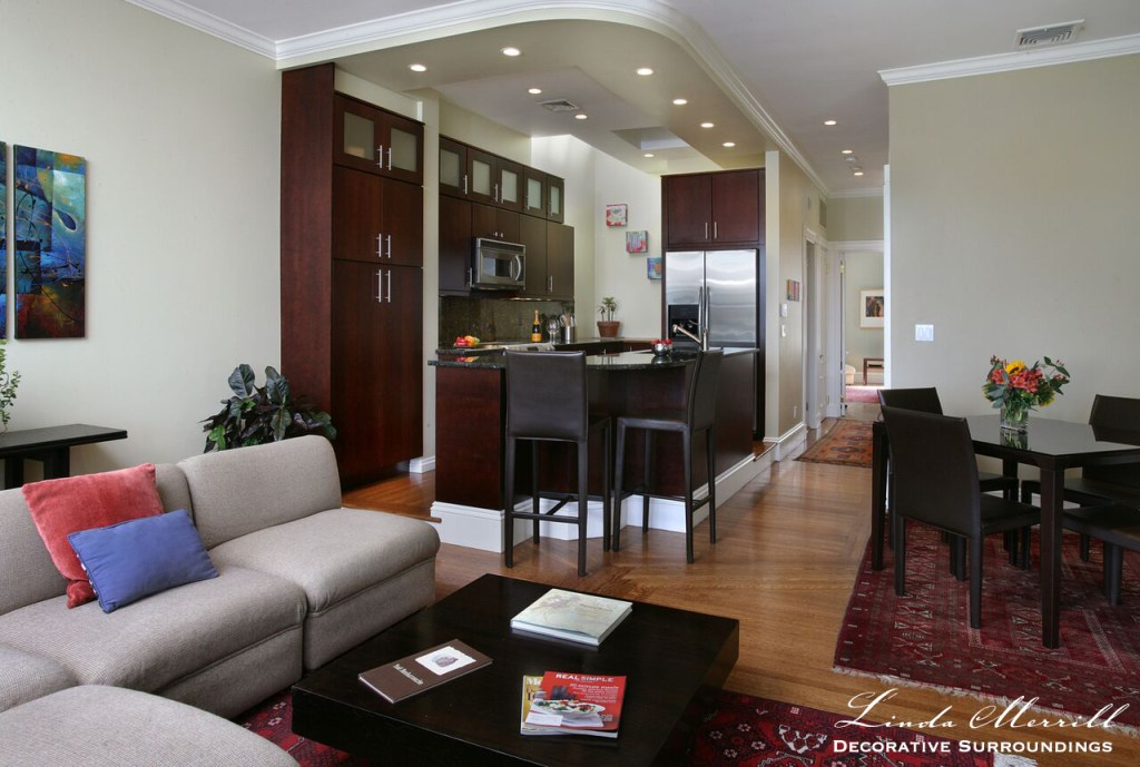 Back Bay Bachelor Penthouse living room and kitchen with beige sectional red oriental carpet,contemporary art, view of Charles River