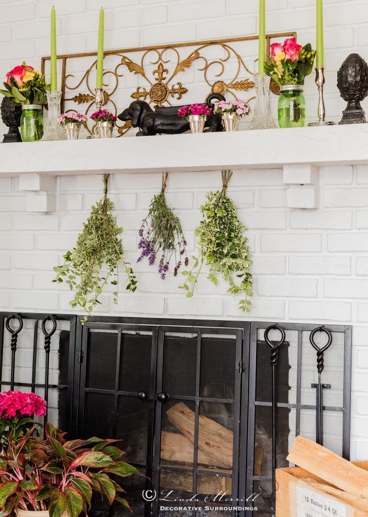 Design by Linda Merrill Decorative Surroundings: Colorful waterfront cottage White brick fireplace with colorful flowers and items on the mantel, black fire screen.
