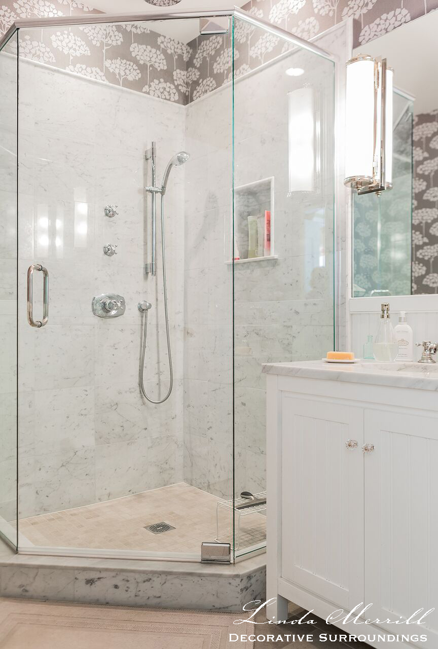 Interior bathroom design by Linda Merrill. White marble shower with glass doors, whit vanity, gray and white Graham and Brown wallpaper with trees, Hubbardton Forge lighting