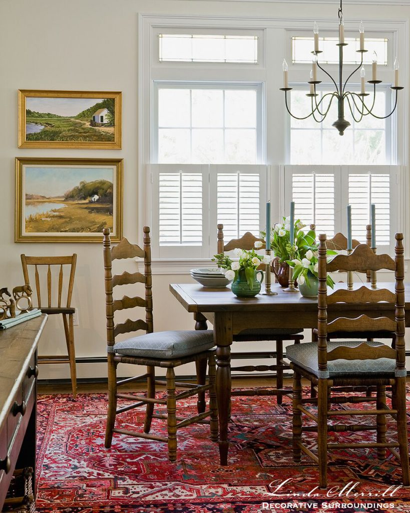Design by Linda Merrill Decorative Surroundings: Coastal Home dining room in Duxbury MA ladder back antique chairs with seat cushions antique table wrought iron chandelier fine art red oriental carpet