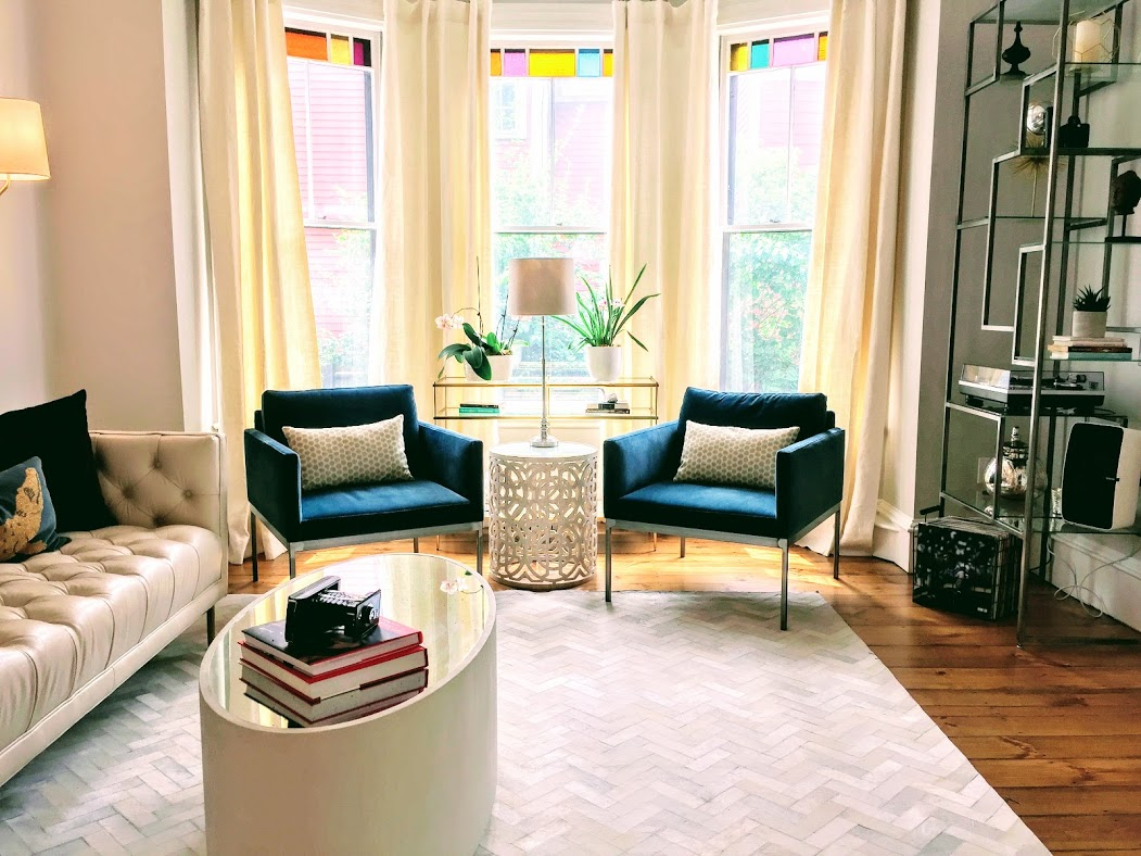 Living room with teal blue chairs, hyde hair rug, cream leather sofa
