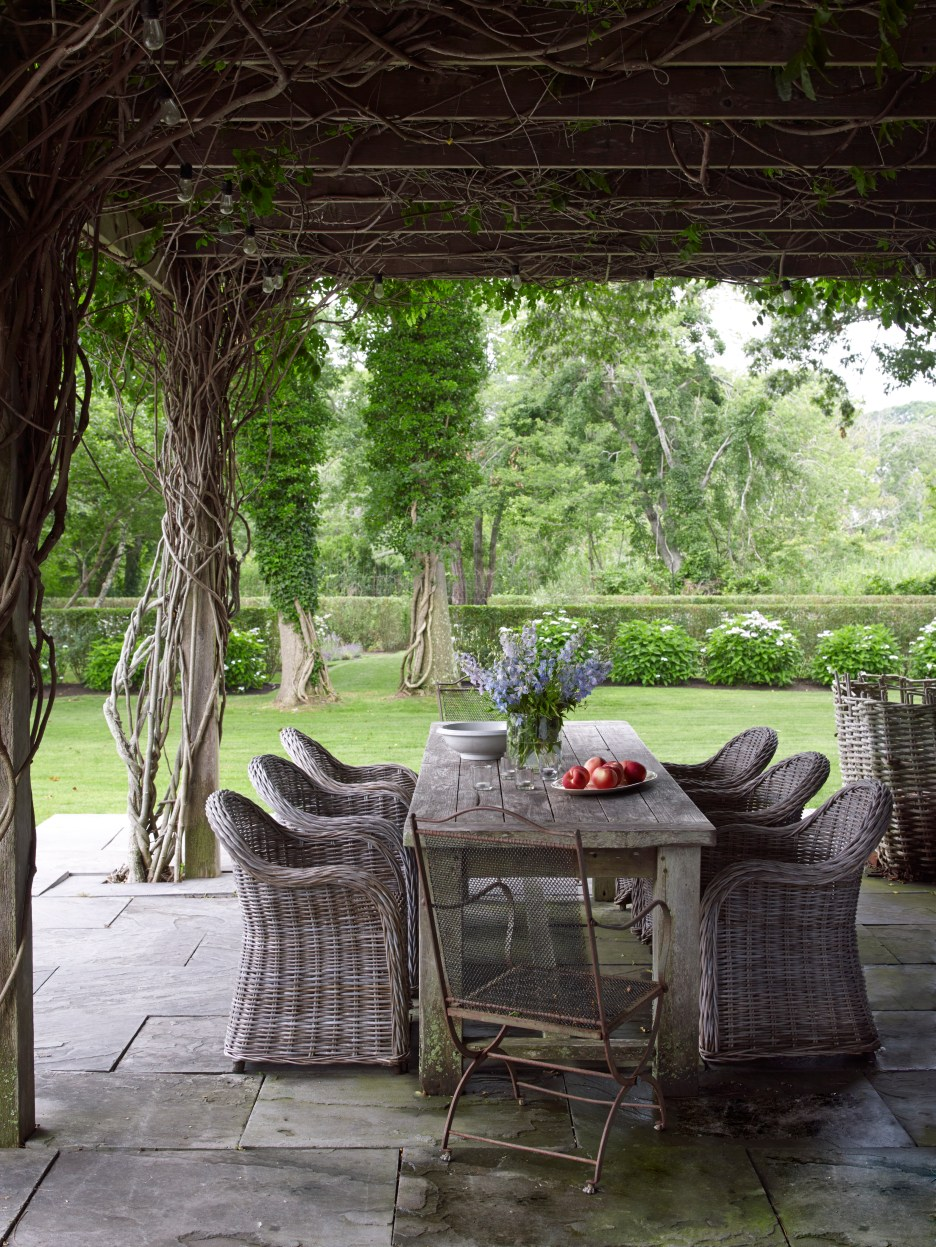 the Hamptons Outdoor dining area under pergola with vines, slate floor, wicker chairs, wood tables, wrought iron chair, green lawn and trees