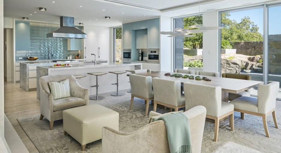 Spectacular oceanside modern beach house in Manchester-By-The-Sea Massachusetts. #modern #beach #coastal #home #oceanside #views #stone #glass #kitchen #modern #stainless #counter #stools #dining #room #diningroom #beige #upholstery #blue #green