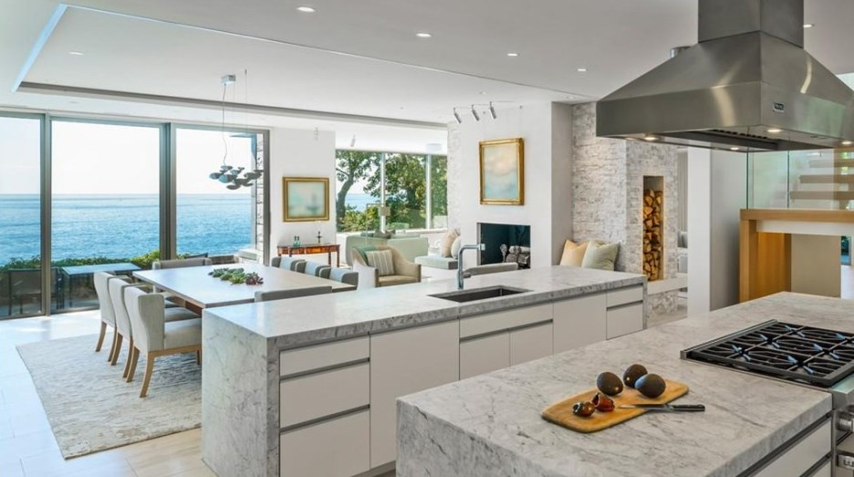 Spectacular oceanside modern beach house in Manchester-By-The-Sea Massachusetts. #modern #beach #coastal #home #oceanside #views #stone #glass #kitchen #dining #room #diningroom #stainless #venthood #views #firewood #box