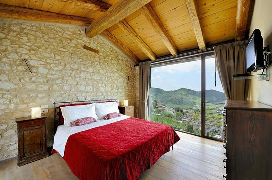 Agritourismo Relais Dolcevista hotel bedroom with red bedding under beamed ceiling with large windows