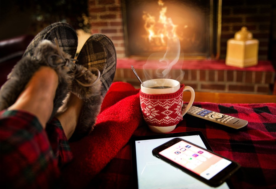Comfy slippered feet up in front of a fire with a cup of coffee, which has a sweater