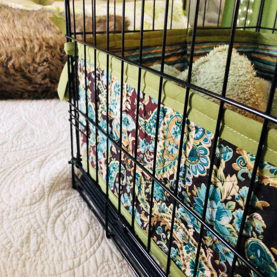Dog crate cover and bumpers green and blue quilted fabric.