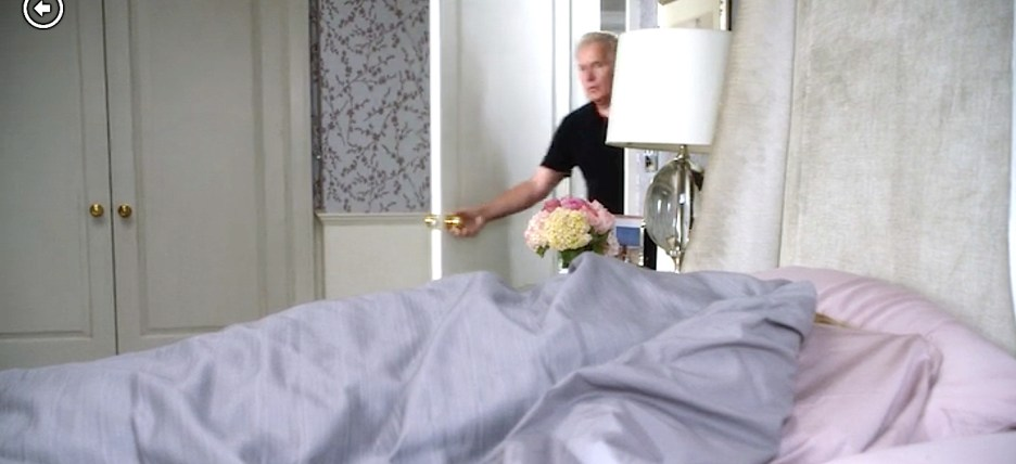Grace and Frankie Jane Fonda bedroom, soft purple wallpaper white woodworking, pink and lavender bedding, crystal lamp, martin sheen as robert walking in