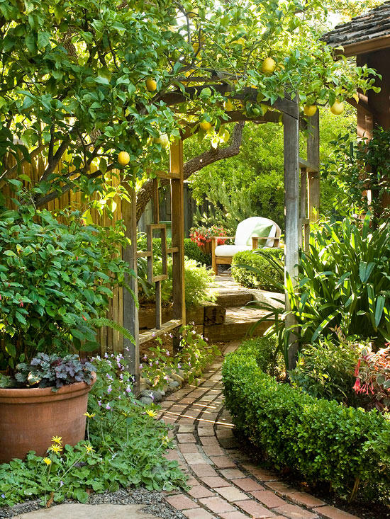 A brick garden path leading under a modern wood arch revealing a sitting area BHG secret garden