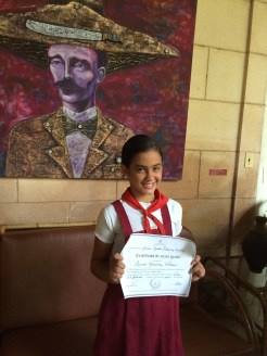 6th grade graduate in front of a portrait of Cuban national hero José Martí