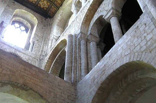 Winchester Cathedral interior, looking up into the north side Romanesque Transept, heavy stone blocks and two stories of thick arches, with tiled and coffered ceiling