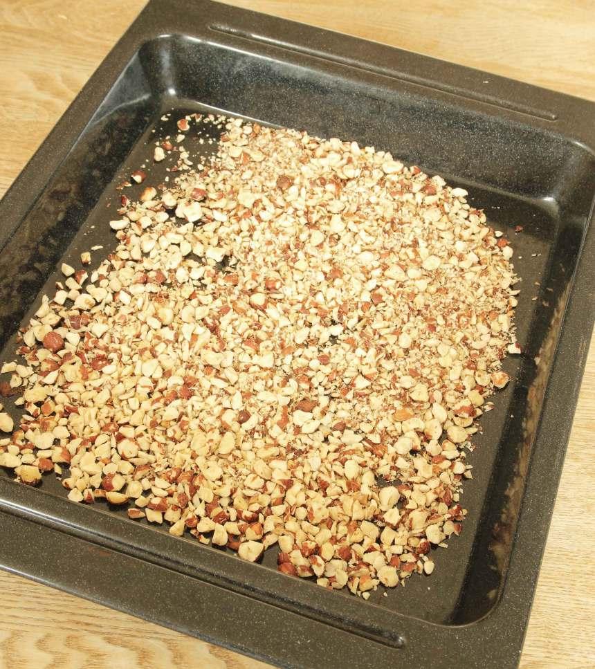 1. Sätt ugnen på 180 grader. Hacka nötterna och lägg dem på en ugnsplåt. Rosta dem mitt i ugnen i 7–10 min. Låt dem kallna på plåten.