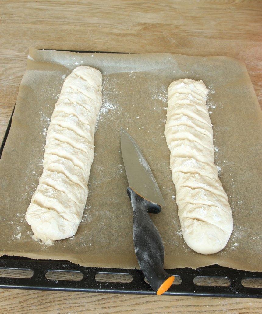3. Skär sneda snitt i baguetterna med en vass kniv. Låt dem jäsa under bakduk i ca 30 min. Sätt ugnen på 250 grader.