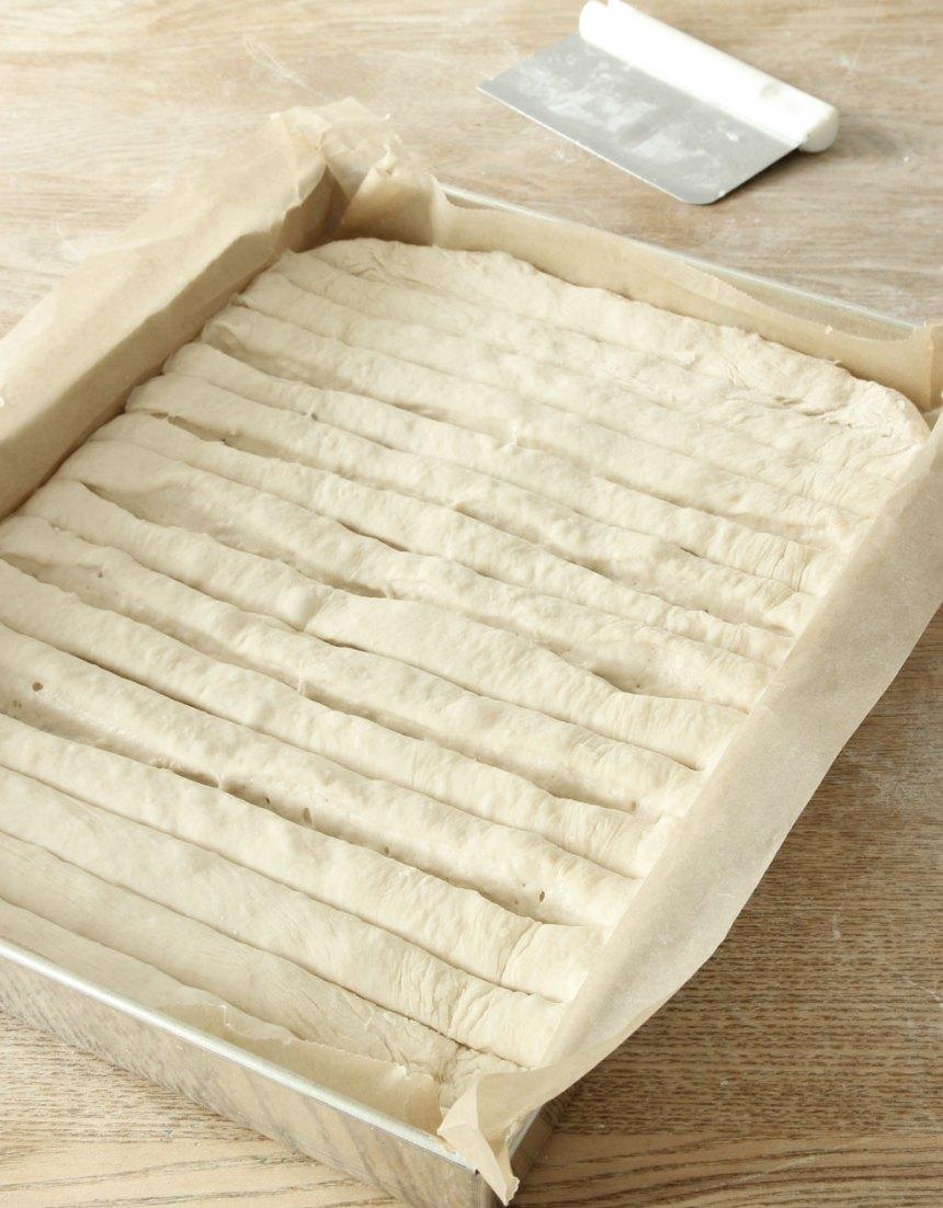 3. Dela degen i ca 2 cm breda längder med en degskrapa. Låt den jäsa i ca 30 min. Sätt ugnen på 250 grader.