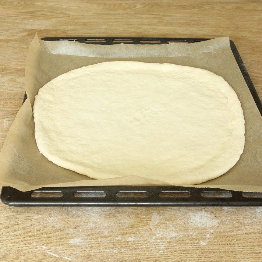 2. Knåda igenom degen på ett mjölat bakbord. Kavla ut den till en rundel, ca 1 ½ cm tjock. Lägg den på en plåt med bakplåtspapper. Låt den jäsa under bakduk i ca 30 min. Sätt ugnen på 250 grader.