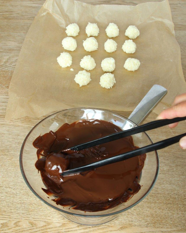 4. Doppa kokosbollarna i chokladen och lägg tillbaka dem på bakplåtspappret.