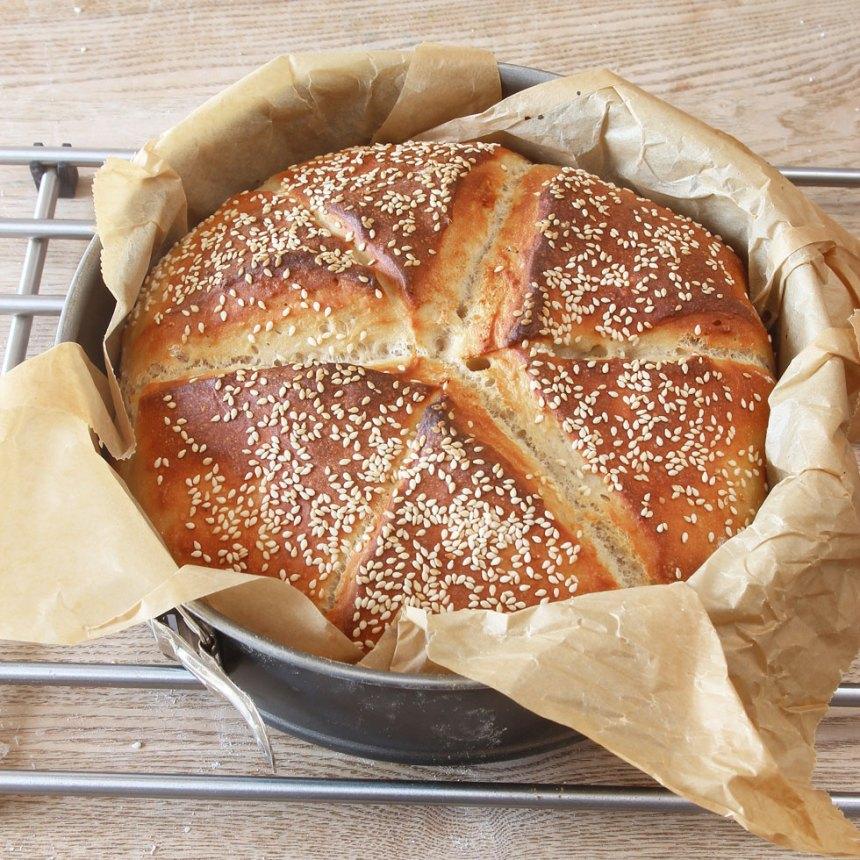 4. Grädda brödet mitt i ugnen i 13–15 min. Sänk värmen till 230 grader när du sätter in brödet. Lyft upp brödet i papperet och låt det svalna under en bakduk.