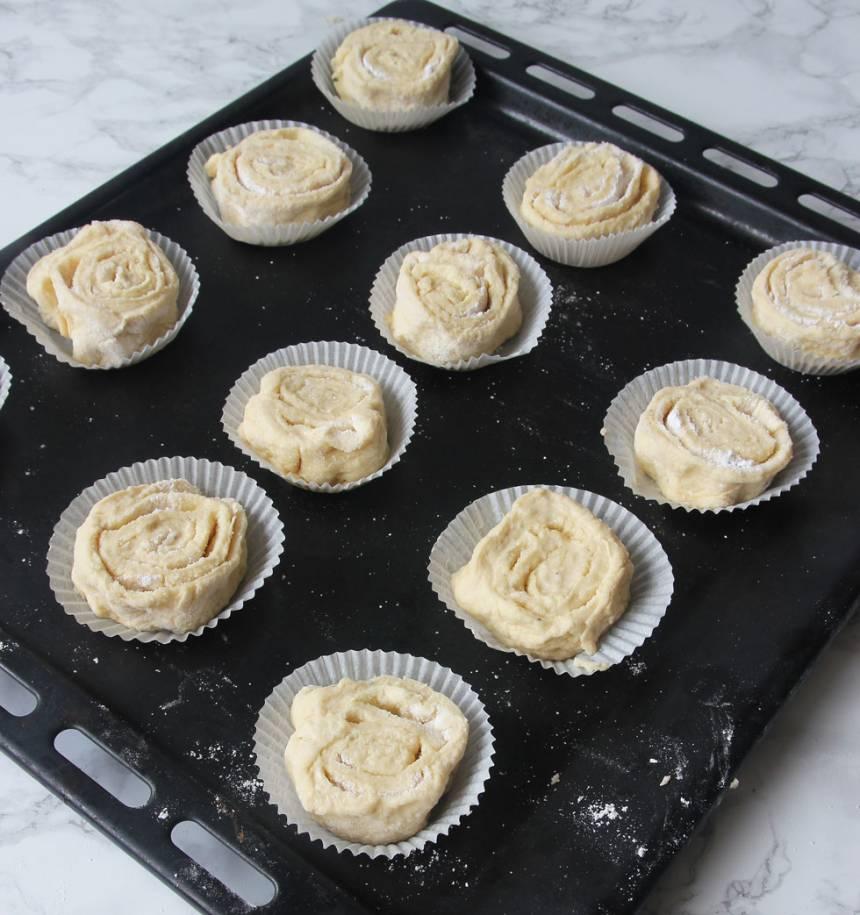 6. Lägg bullbitarna i pappersformar på en plåt. Låt dem jäsa under bakduk i ca 30 min. Sätt ugnen på 250 grader.