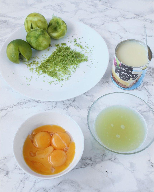 4. Fyllning: Sätt ugnen på 150 grader. Vispa ihop äggulorna lätt i en skål med en vanlig handvisp. Finriv ca 1 msk limeskal. Pressa ur 1 dl limejuice från limefrukterna. Öppna burken med kondenserad mjölk.