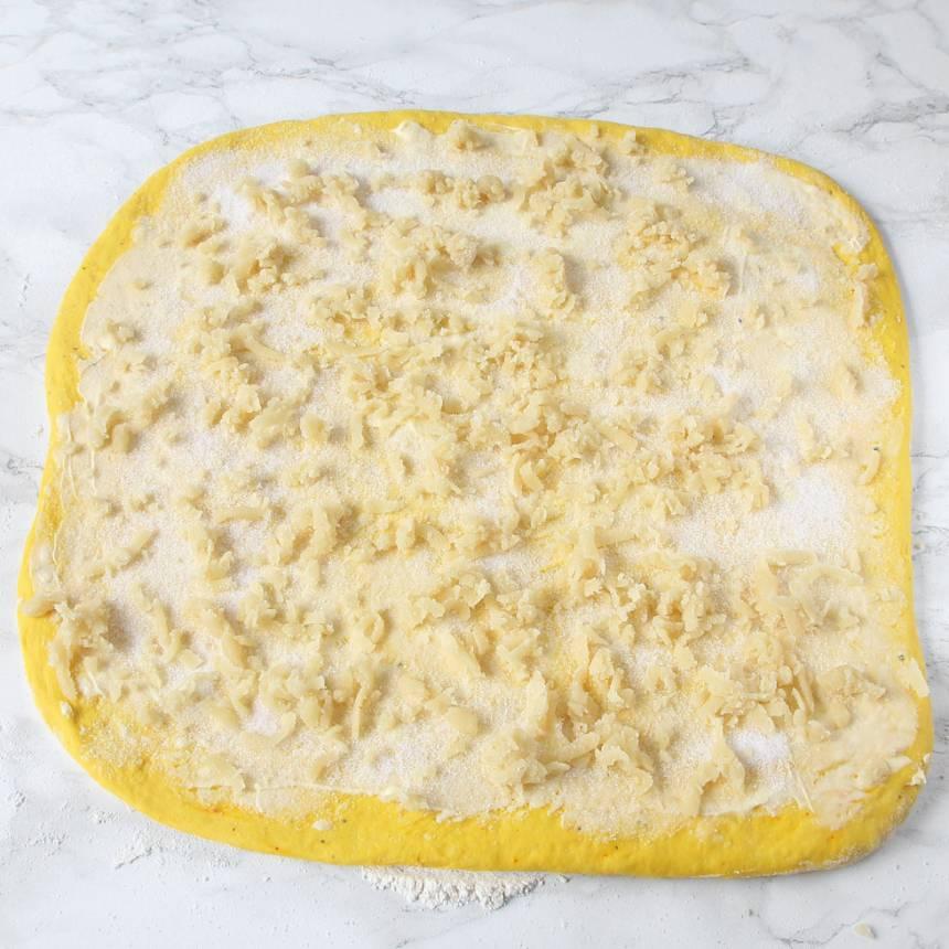 4. Bred ut hälften av smöret på degplattan och strö över hälften av strösockret och vaniljsockret. Strö över mandelmassan (eller vaniljsocker/vit choklad).