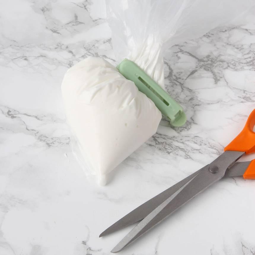 3. Lägg smeten i en liten plastpåse. Knyt ihop den och klipp ett hål i ena hörnet.