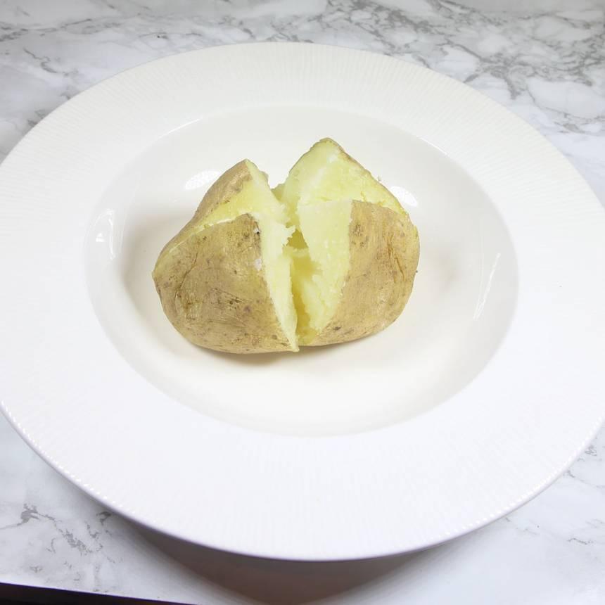1. Stick några hål i potatisen med en potatissticka. 2. Kör potatisen på högsta effekt i 10–15 minuter, beroende på storlek. Den ska vara ordentligt mjuk rakt igenom. Om du kör flera potatisar på en gång tar det längre tid. 3. Skär ett kryss i potatisen med en vass kniv. Tryck ihop den med fingrarna från sidorna så att krysset öppnar sig. Lägg i en god röra eller en klick smör.