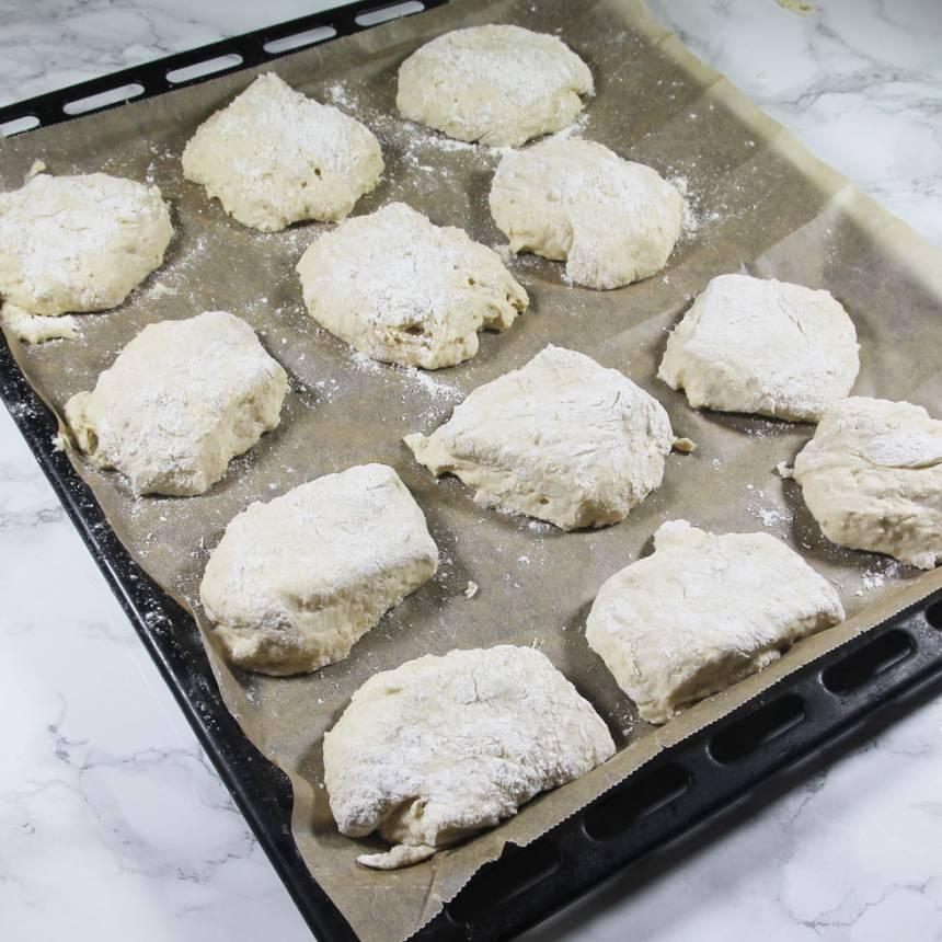 4. Lägg degbitarna på en plåt med bakplåtspapper. Strö över lite mjöl. Täck frallorna med plastfolie och låt dem jäsa i kylen över natten.