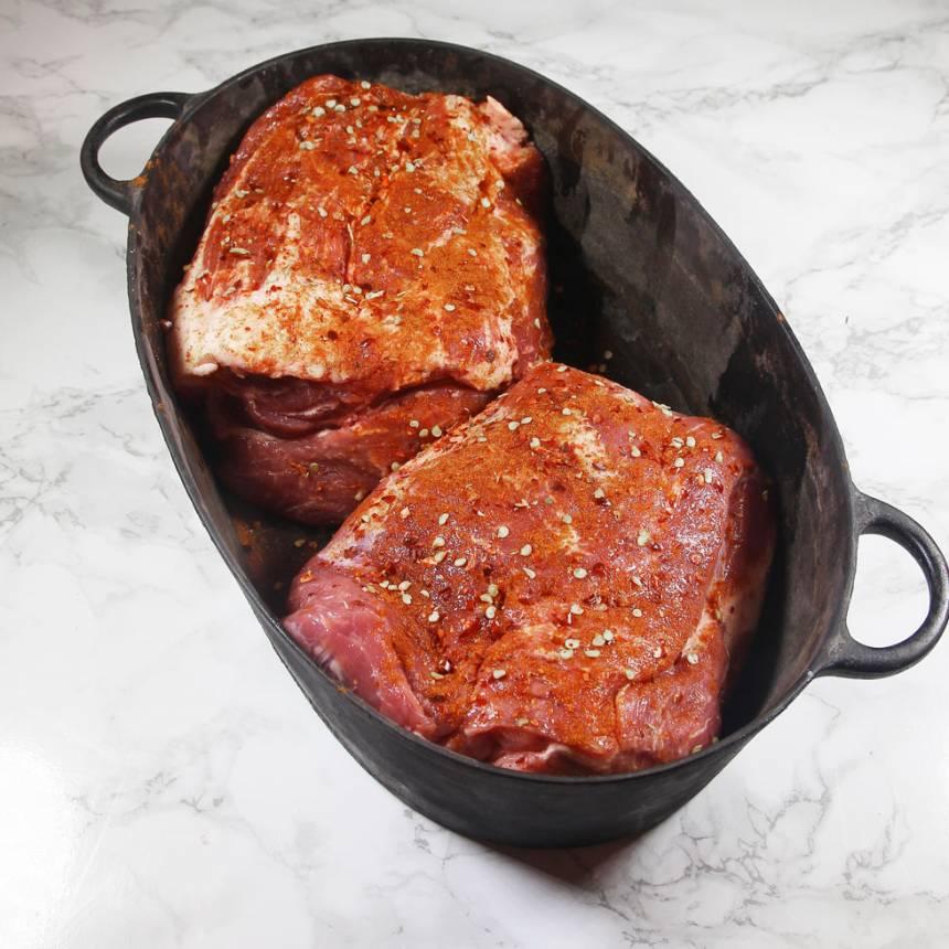 1. Sätt ugnen på 100 grader. Krydda fläskkarrén med salt, chiliflakes, paprikakrydda och chilipulver. Lägg köttet i en gjutjärnsgryta. Pressa vitlöken ner i grytan.