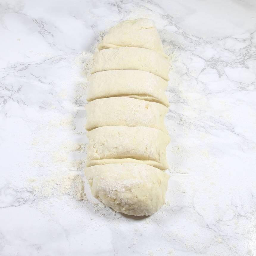 2. Rulla degen i vetemjöl och rulla ut den till en längd. Dela den i 6 bitar.