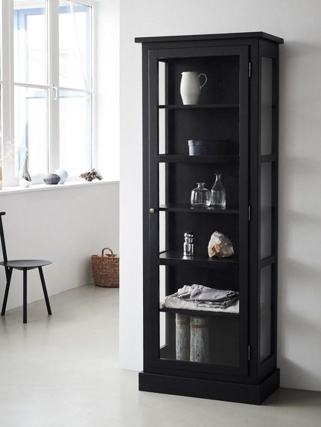 Billede af Lindebjerg Design Dark Oak N1 vitrineskab i en hvidfarvet gang med interiør