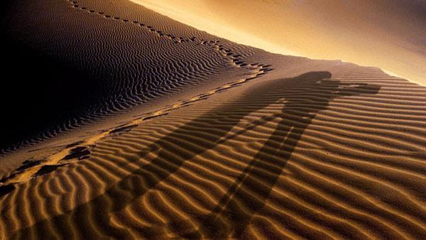 Schatten eines Kameramannes auf Wüstendünen