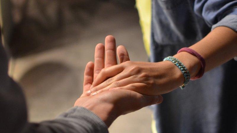 helfende Hände, zwei Menschen geben sich die Hand