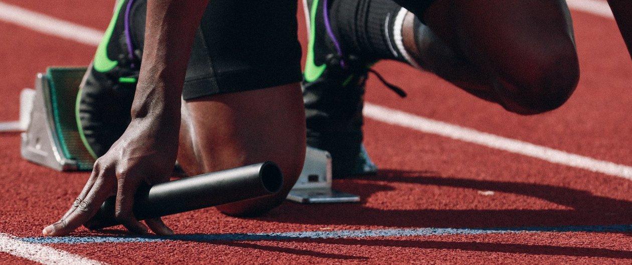 Läufer im Starterblock mit Staffelstab