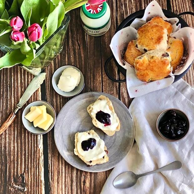 Korb mit Scones mit Rosinen und ein Teller mit bestrichenen Hälften auf Holzplanken mit Butter; Clotted Cream und Tulpen