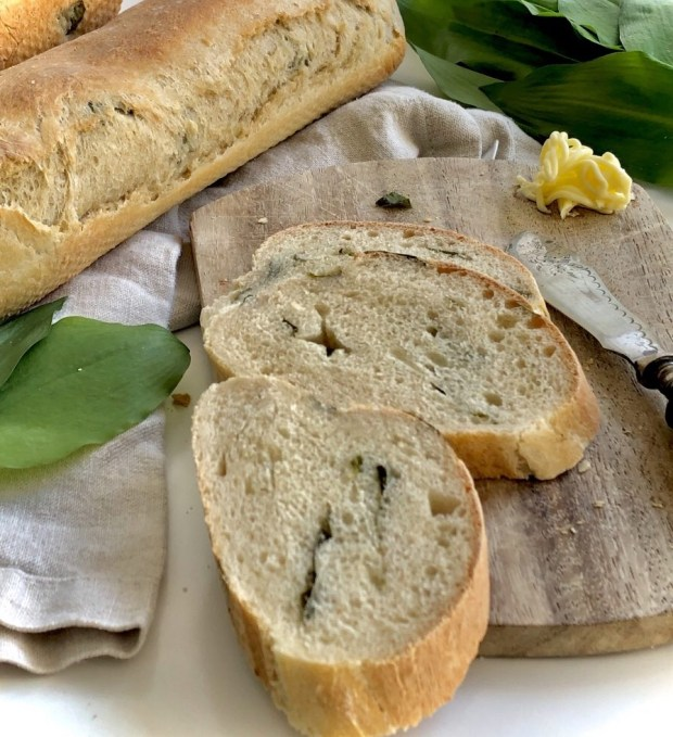 Aufgeschnittenes Bärlauch-Baguette  auf  einem Holzbrett mit Bärlauch-Blättern und Butter